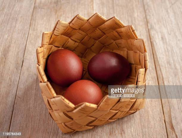 red colored spring easter eggs in a basket from bast on natural wooden background - orthodox easter stock pictures, royalty-free photos & images