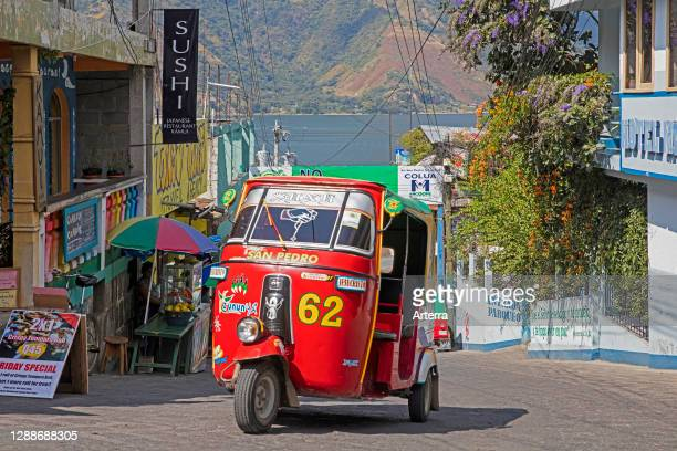 Red coloured tuk-tuk / mototaxi in the town San Pedro La Laguna near Lago de Atitlan / Lake Atitlan, Solola Department, Guatemala, Central America.