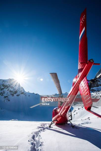 red commercial helicopter in the mountains - helicopter photos stock pictures, royalty-free photos & images