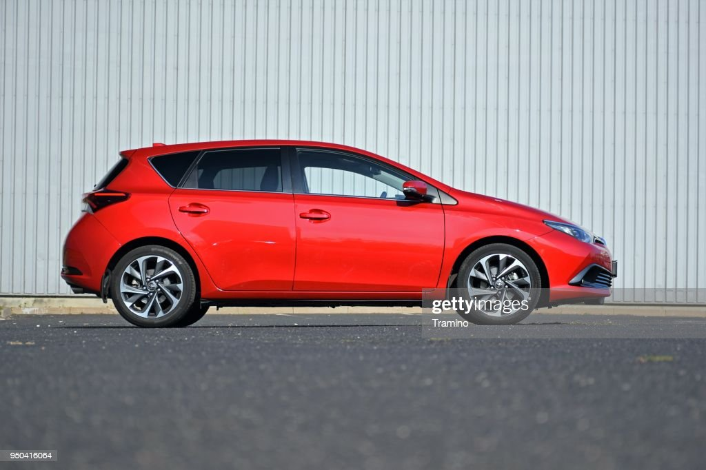 Red compact car on the street : Stock Photo