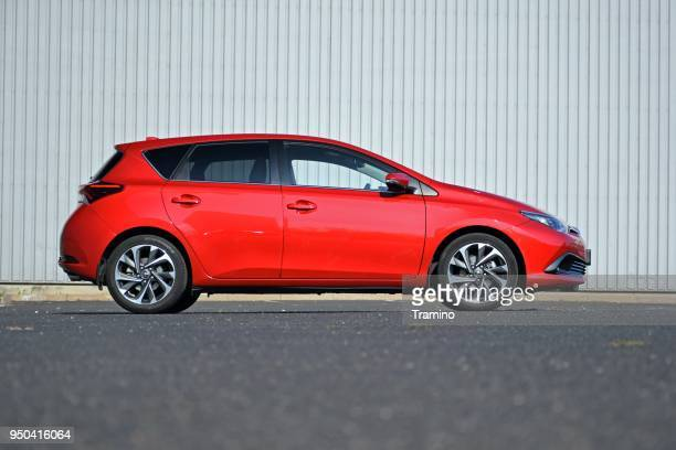 red compact car on the street - compact car stock photos and pictures