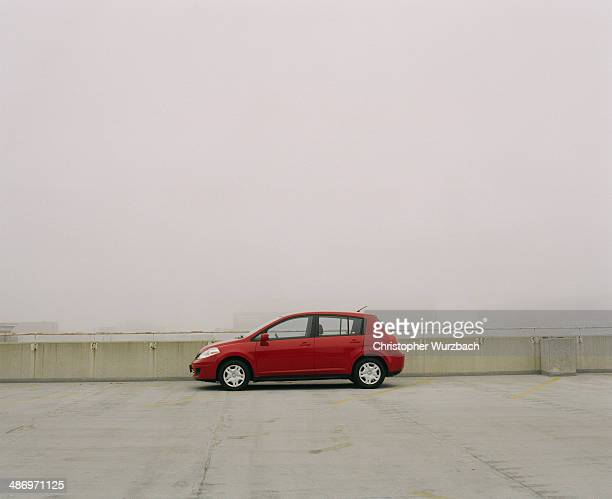 Red compact car on top of parking garage in fog