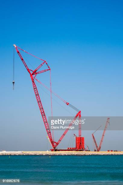 red construction crane - on a beach area in dubai, united arab emirates. - claire plumridge stock pictures, royalty-free photos & images