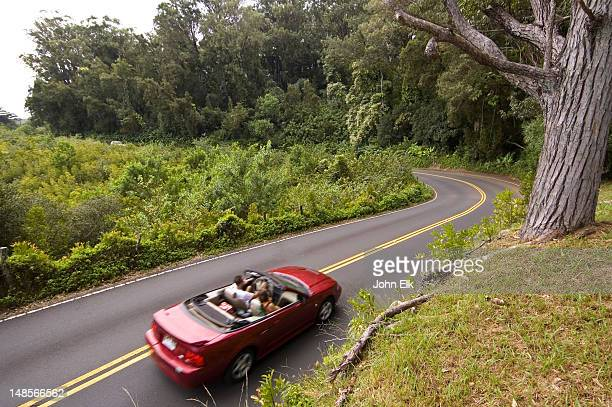 Red convertible driving on Hana highway.