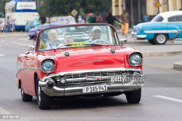 Red convertible old American Chevrolet taxi carrying passengers on busy road Vintage cars are a tourist attraction in the Caribbean island