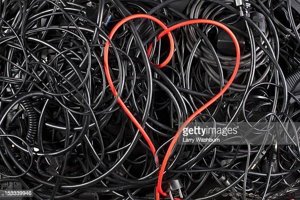 A red cord in a heart shape amongst tangled black cables and cords