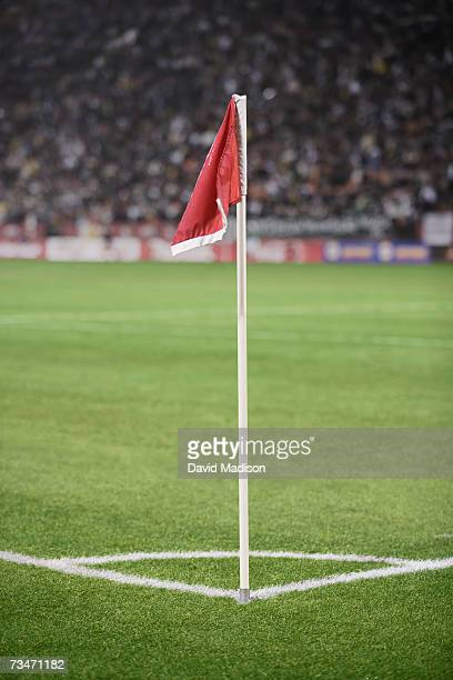 Red corner flag on a soccer field with spectators in background