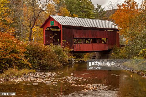 red covered bridge in vermont in autumn - covered bridge stock photos and pictures
