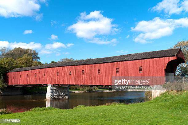 red covered bridge - covered bridge stock photos and pictures