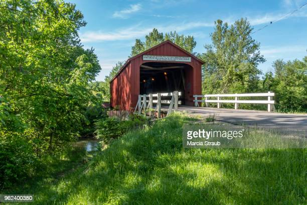 red covered bridge - covered bridge stock pictures, royalty-free photos & images