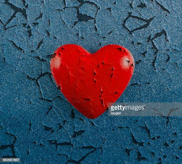 red cracked heart on blue background - blood love stock photos and pictures