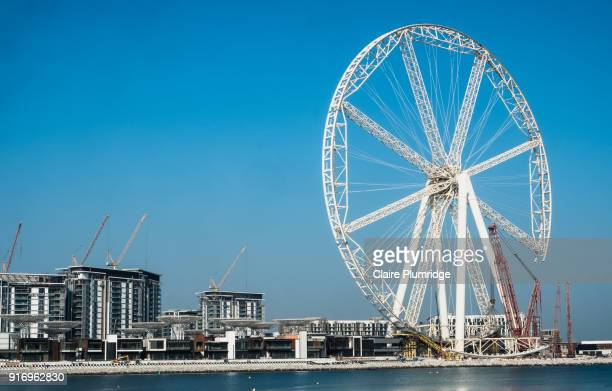 red crane used in the construction of the ain dubai ferris wheel, dubai, united arab emirates. - claire plumridge stock pictures, royalty-free photos & images