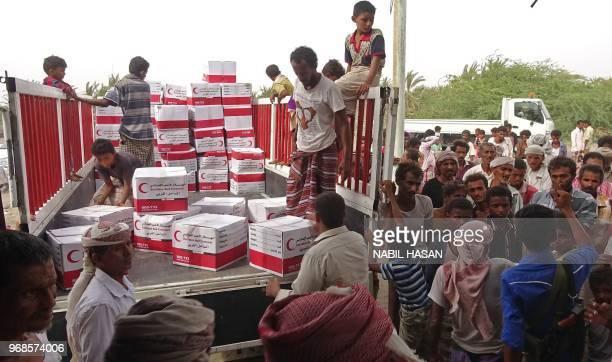 UAE red crescent members distribute food aid in the village of Al Mujaylis western Yemen on June 6 2018