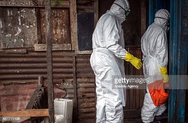 Red cross health workers who wear protective gear prepare to move the body of 67yearold Jenneh Momoh died due to Ebola virus in Caldwell town of...
