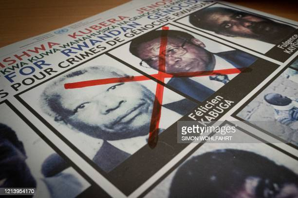 A red cross is seen drawn on the face of Felicien Kabuga one of the last key suspects in the 1994 Rwandan genocide on a wanted poster at the Genocide...