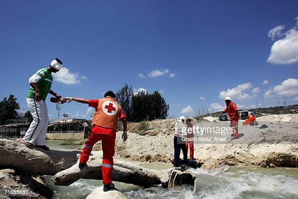 Red Cross medics help injured Hezbollah fighters cross a make shift bridge on the Litani river August 09 2006 in Qassimiya few kilometers north of...
