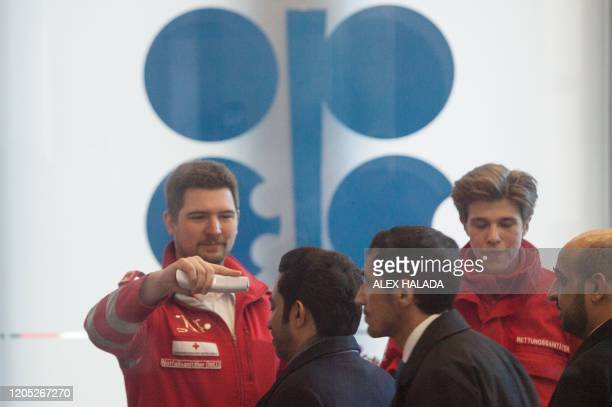 Red Cross medics measure the temperature of participants of the 178th Organization of Petroleum Exporting Countries meeting in Vienna Austria on...