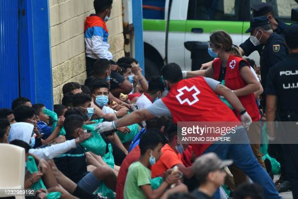 Red Cross members assist migrant minors as they wait to be tested for COVID-19 upon their arrival to the Spanish enclave of Ceuta, on May 19, 2021. -...