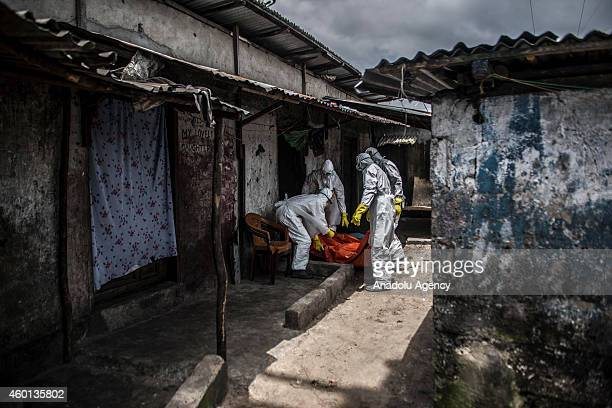 Red Cross members carry dead body of Mambodou Aliyu died due to the Ebola virus,, in Monrovia, Liberia on 15 October, 2014.