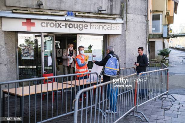 Red Cross members give food to people in need close to the market area on March 20, 2020 in Annecy, France. Coronavirus has spread to over 156...