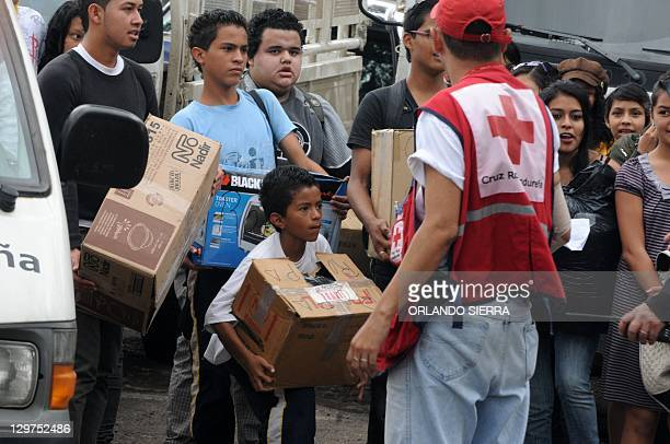 Red Cross personnel hand on relief aid for refugees from the floods in Tegucigalpa on March 20 2011 Health authorities warned Wednesday of virus...