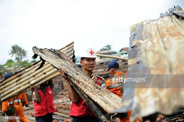 Red Cross rescue workers clear debris from destroyed houses following days of sectarian violence in Sittwe, capital of Myanmar's western state of...