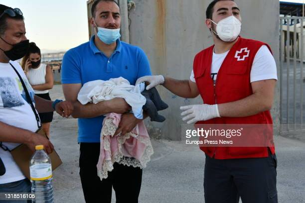 Red Cross staff attend to migrants after their arrival at the beach of Tarajal from Morocco on May 17, 2021 in Ceuta, Spain. More than 3,000 Moroccan...