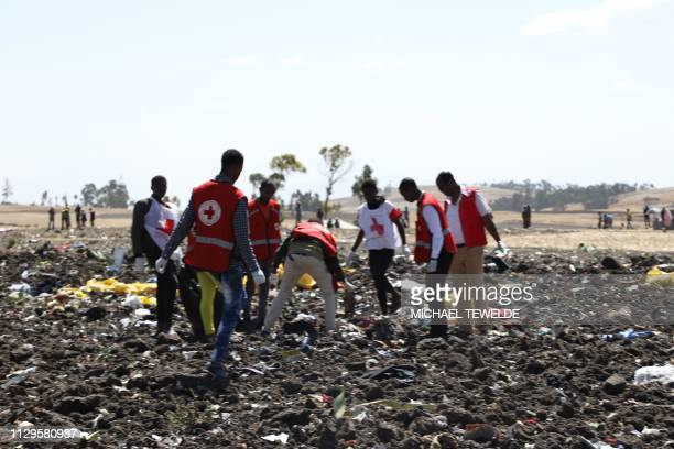 Red cross team work amid debris at the crash site of Ethiopia Airlines near Bishoftu a town some 60 kilometres southeast of Addis Ababa Ethiopia on...