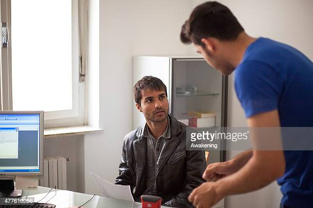 Red Cross translator helps a migrant fill out forms before a medical examination on June 18 2015 in Gorizia Italy Approximately 50 migrants enter...