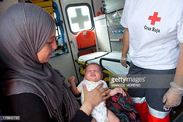 A Red Cross volunteer attends to an infant at a child care centre in the port of Algeciras on August 5 2013 The port of Algeciras over the weekend...