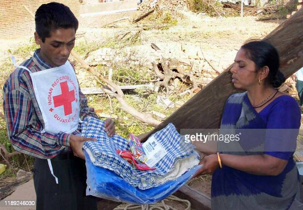 Red Cross volunteer gives a relief package to a woman in Golathara, 19 February some 65 kms from Ahmedabad following a heavy storm which killed 4 and...