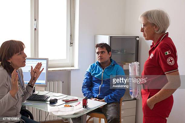 Red Cross volunteer helps with interviewing and filling out migrant forms for a medical examination on June 18 2015 in Gorizia Italy Approximately 50...