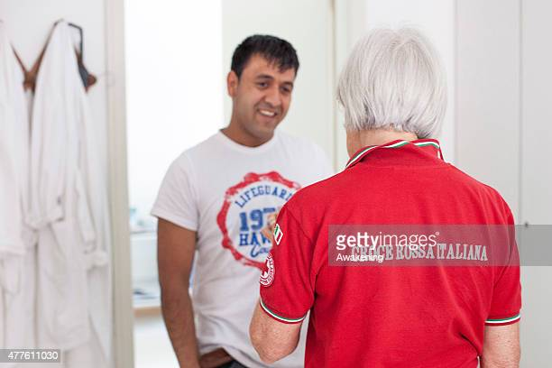 Red Cross volunteer interviews a migrant before a medical examination on June 18 2015 in Gorizia Italy Approximately 50 migrants enter Italy through...