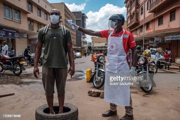 Red Cross volunteer measures the temperature of a man before he can enter Nakasero market in Kampala, on April 1, 2020. - Ugandan President Yoweri...