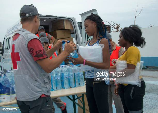 Red Cross volunteers distribute water to people after the passage of Hurricanes Irma and Maria on September 20 2017 in Anse Marcel on the French...