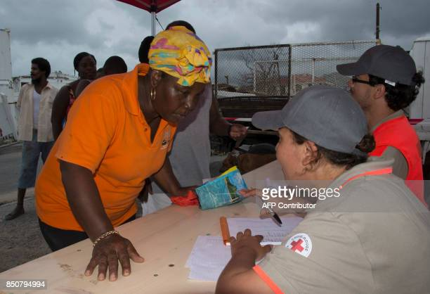 Red Cross volunteers provide aide to a woman after the passage of Hurricanes Irma and Maria on September 20 2017 in Anse Marcel on the French...