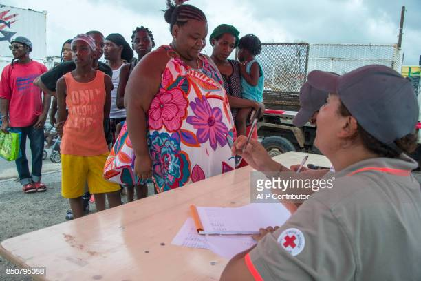 Red Cross volunteers provide aide to locals after the passage of Hurricanes Irma and Maria on September 20 2017 in Anse Marcel on the French...