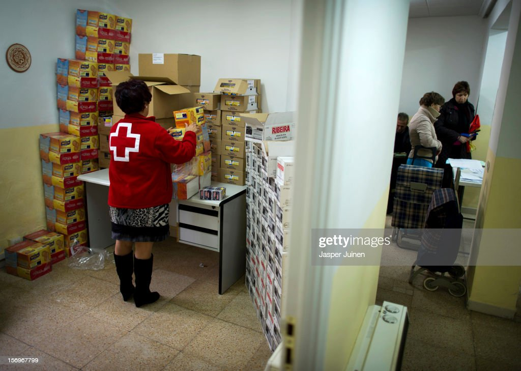 A Red Cross worker arranges boxes with biscuits while unemployed Spaniards (R) wait in line for a food hand out inside a Red Cross post on November 23, 2012 in Villacanas, Spain. During the boom years, where in its peak Spain built some 800,000 houses a year accompanied by the manufacturing of millions of wooden doors where needed, the people of Villacanas were part of Spain's middle class enjoying high wages and permanent jobs. During the construction boom years the majority of the doors used within these new developments were made in this small industrial town. Approximately seven million doors a year were once assembled here and the factory employed a workforce of almost 5700 people, but the town is now left almost desolate with the Villacanas industrial park now empty and redundant. With Spain in the grip of recession and the housing bubble burst, Villacanas is typical of many former buoyant industrial Spanish towns now struggling with huge unemployment problems.