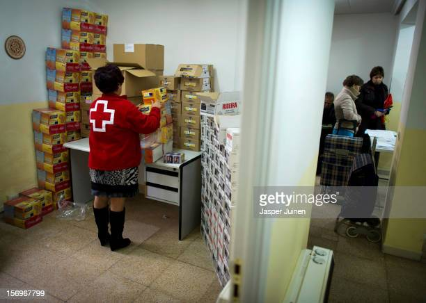 Red Cross worker arranges boxes with biscuits while unemployed Spaniards wait in line for a food hand out inside a Red Cross post on November 23 2012...