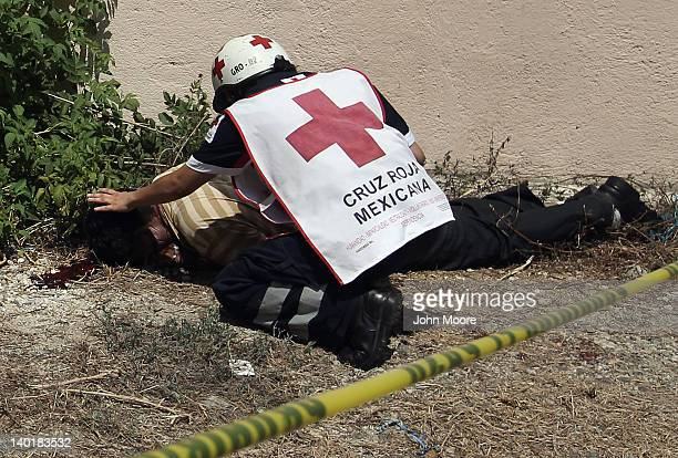 Red Cross worker checks the victim of an apparent drug-related execution on February 29, 2012 in Acapulco, Mexico. Drug violence surged in the...