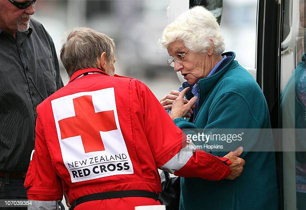 Red Cross worker helps one of the missing miner's family members off the bus after visiting the mine site on November 21 2010 in Greymouth New...