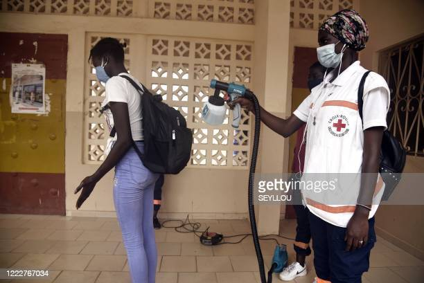 Red Cross worker sprays a pupil with a disinfectant at the entrance of a school in Dakar on June 25 on the opening day of the classes for the...