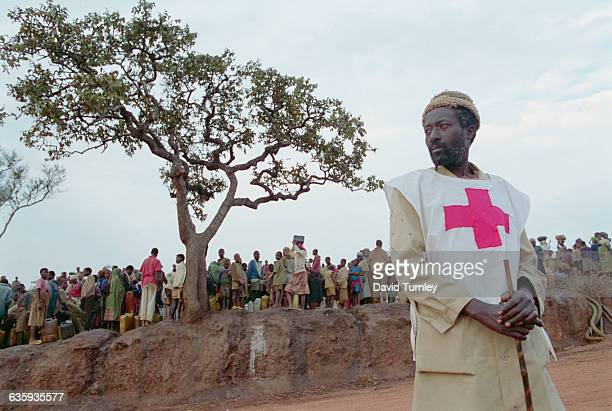 A Red Cross worker stands near Hutu refugees waiting to get water in the Benaco Refugee Camp