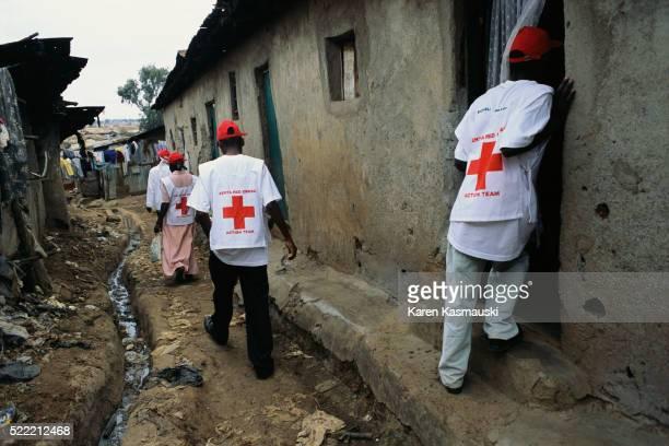 red cross worker telling villagers about measles vaccine - croce rossa organizzazione foto e immagini stock