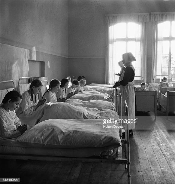 Red Cross workers and Protestant relief workers care for orphaned children many of whom lost their parents in World War II The children sit in bed...