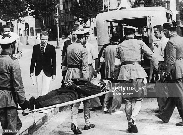 Red Cross workers carry a victim of the Civil War fighting in Barcelona by stretcher to a waiting ambulance | Location Barcelona Spain