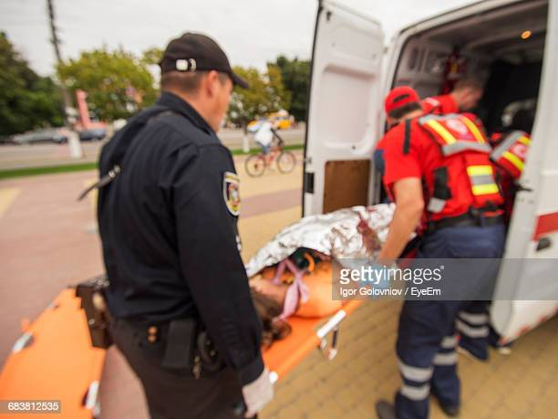 red cross workers carrying wounded person to ambulance - 赤十字社 ストックフォトと画像