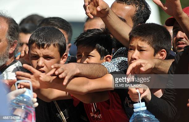 Red Cross workers give out water as migrants and refugees wait under the sun at a railway station near the official border crossing between Serbia...