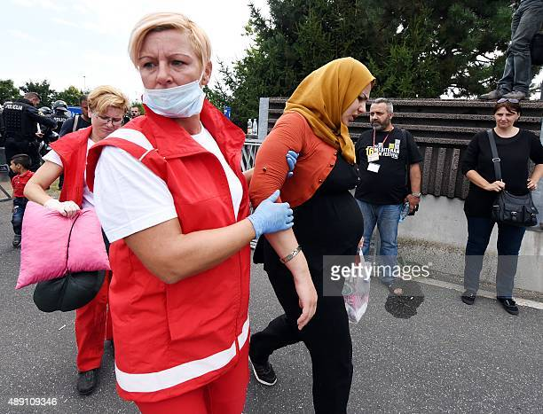 Red Cross workers help a pregnant woman as migrants and refugees wait to depart at the bridge between the CroatianSlovenian border in Rigonce on...