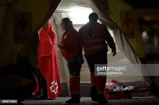 Red Cross workers stand next to a migrant keeping warm inside a tent upon his arrival to the southern Spanish port of Malaga on December 30 2017...